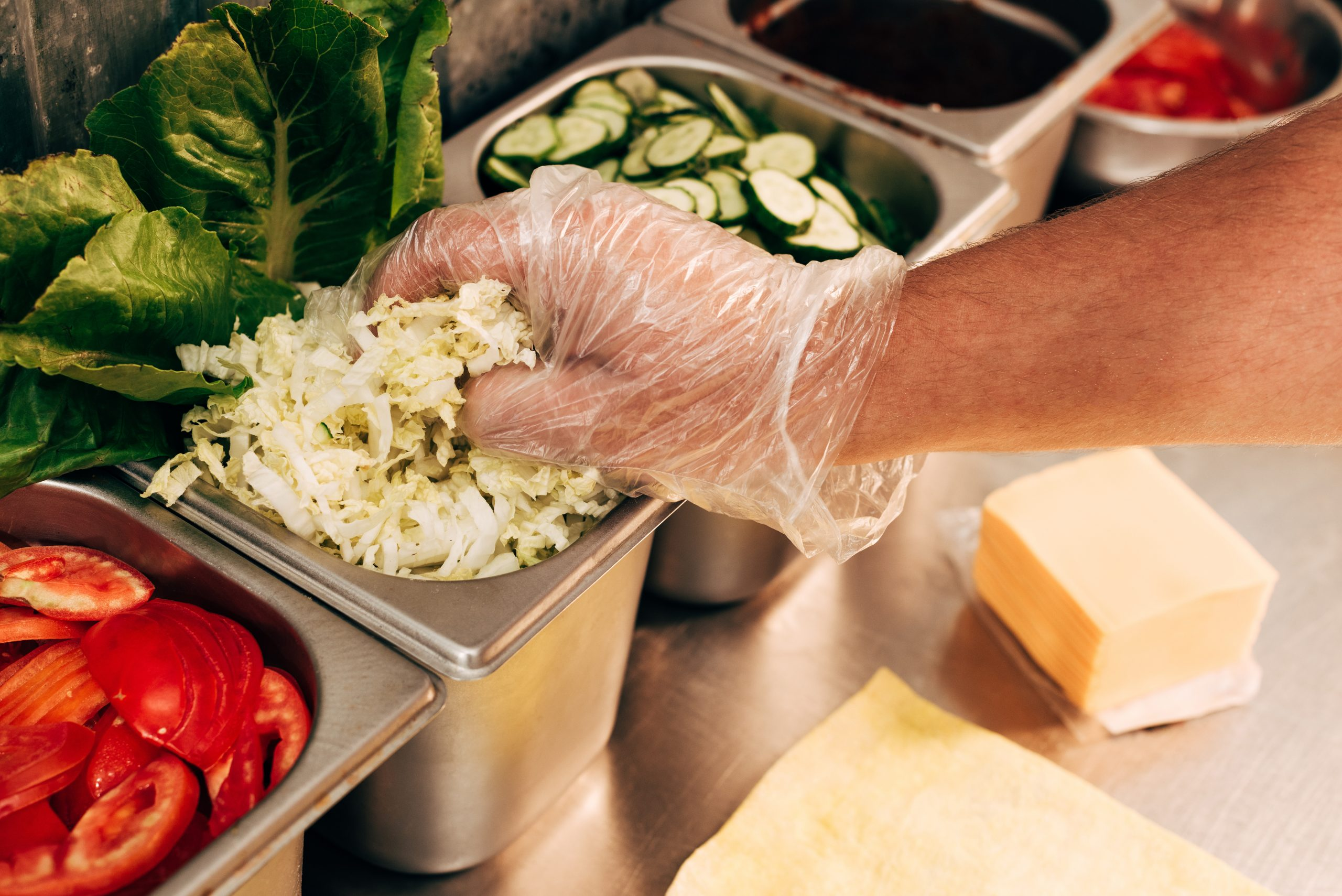 Partial View Of Cook In Glove Holding Cut Lettuce At Workplace