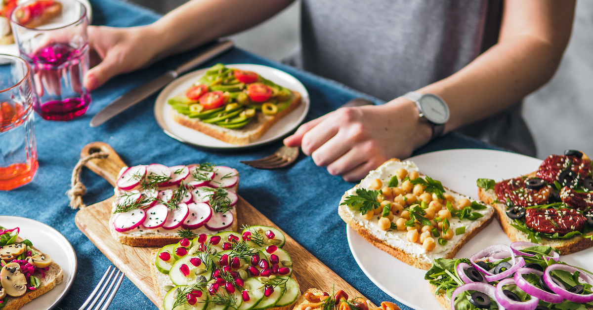 Female Hands On Dinning Table. Young Woman Eat Vegetarian Toast. Vegan Veggies Sandwiches On Dinning
